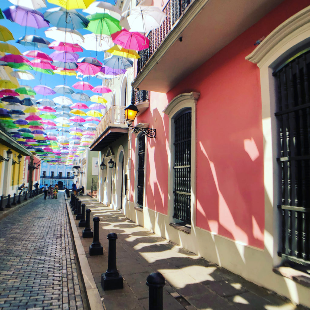 A Picture of Calle Fortaleza Old San Juan with many colored umbrellas suspended across the street