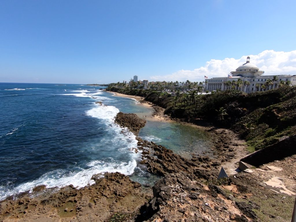 A picture of El Capital, Puerto Rico's Capital building and the shoreline of the Atlantic Ocean as seen form the U. S. National Park Service's fort Castillo de San Cristobal