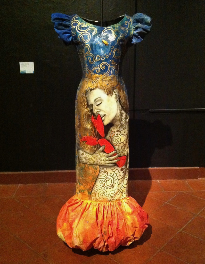 A picture of a dress that has been over painted by an artist at the Fashion Art Exhibit at Museo de Las Americas