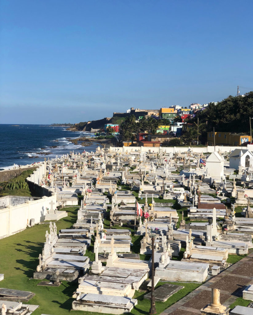 A picture of Cementerio Santa Maria Magdalena with grave stones in the foreground, La Perla neighborhood and historic bastions and fort walls in the distance. Old San Juan, Puerto Rico.