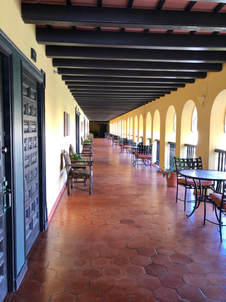 A picture of An Open Corridor at Hotel El Convento with tiled floors and bistro tables and chairs