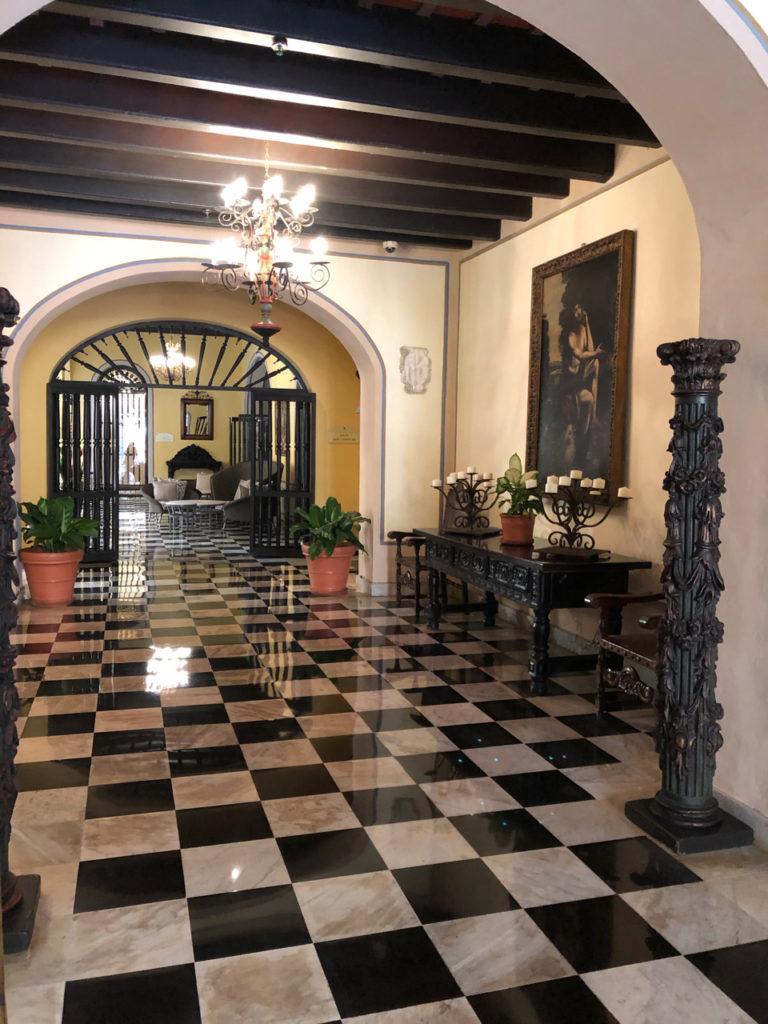 A picture of the lobby with black and white tiles and artwork in the Hotel El Convento in Old San Juan