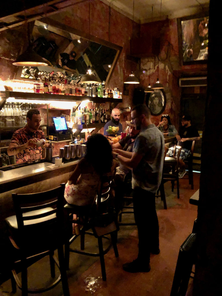 A Picture of a small bar with customers and bartender at La Factoria in Old San Juan