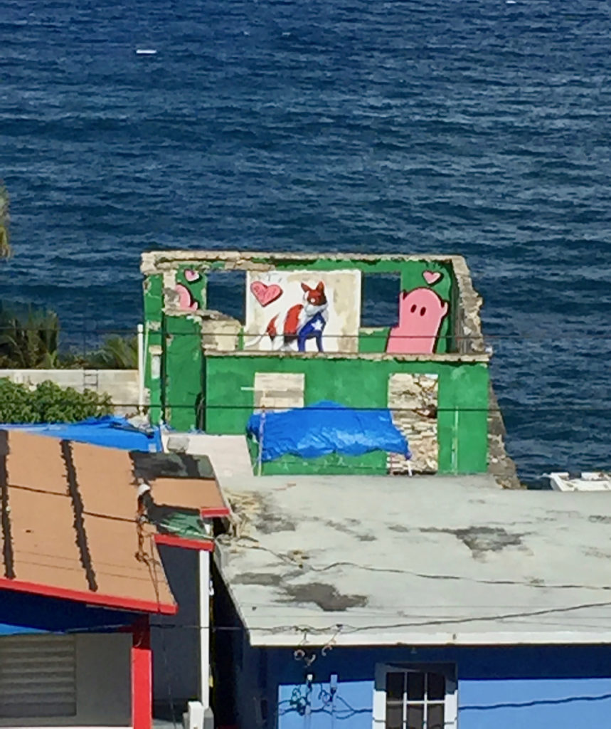 A picture of some colorful buildings and the Atlantic Ocean. One building is painted with graffiti in La Perla, Old San Juan, Puerto Rico