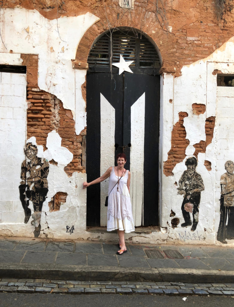A picture of One Day Woman on the street in front of a large door representing the Puerto Rican Flag but in black and white instead of blue red and white